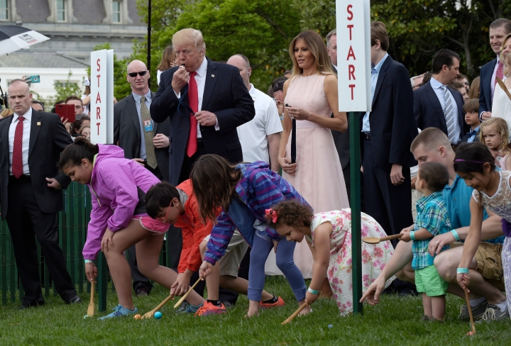 FILE - In this April 17, 2017, file photo, President Donald Trump, accompanied by first lady Melania Trump, blows a whistle to begin an Easter Egg Roll race on the South Lawn of the White House in Washington during the annual White House Eastern Egg Roll. The White House is opening the gates for its biggest social event of the year, the annual Easter Egg Roll. Trump and his wife, Melania, are hosting festivities Monday, April 2, 2018, on the South Lawn for a crowd of nearly 30,000 adults and children. (AP Photo/Susan Walsh, File)