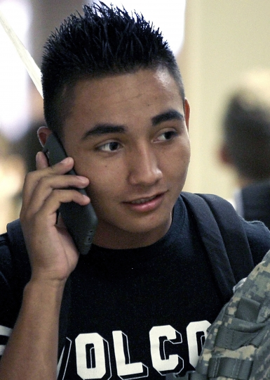 FILE - In this Aug. 3, 2016 file photo, Jeffersonville High School junior Martin Ojeda talks with a friend on the phone between classes at the school in Jeffersonville, Ind., where students at the are allowed to use phones during the day. Cellphones are still absent from most U.S. schools but new data shows them steadily gaining acceptance as administrators bow to parents' wishes to keep tabs on their kids and teachers find ways to work them into lessons. (Jerod Clapp/News and Tribune via AP, File)
