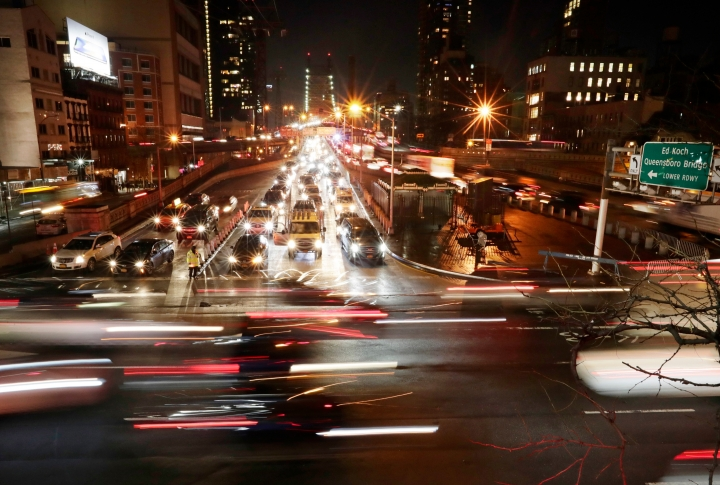 """FILE- In this Jan. 11, 2018, file photo, cars pass the Queensboro Bridge in New York. Environmental regulators announced on Monday, April 2, 2018, they will ease emissions standards for cars and trucks, saying that a timeline put in place by President Obama was not appropriate and set standards """"too high."""" (AP Photo/Frank Franklin II, File)"""