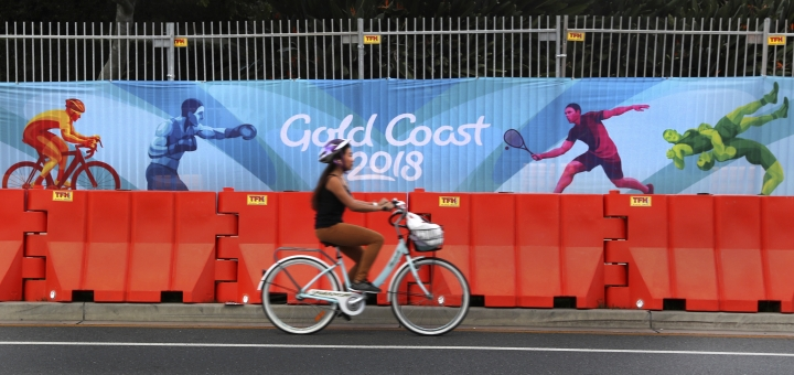 A cyclist rides past Commonwealth Games banner on the side of the road in Gold Coast, Australia, Monday, April 2, 2018. The 2018 Commonwealth Games will be taking in Gold Coast in Australia from April 4 to 15.(AP Photo/Manish Swarup)