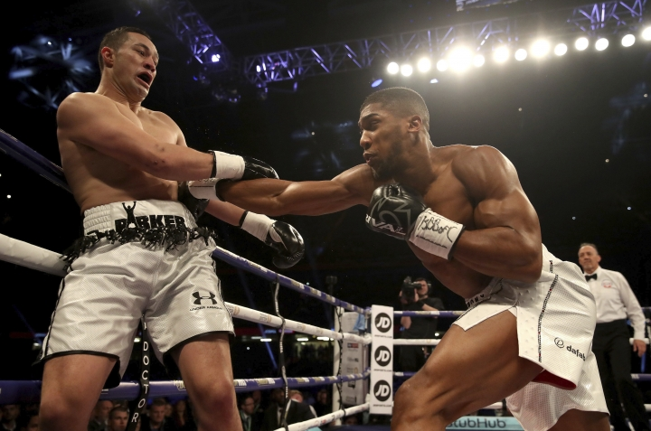 Anthony Joshua, right, battles against Joseph Parker during their WBA, IBF and WBO heavyweight champion at the Principality Stadium in Cardiff, Wales, Saturday March 31, 2018. (Nick Potts/PA via AP)