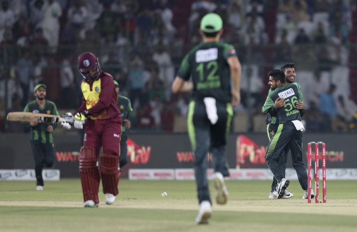Pakistani bowler Shadab Khan, right, celebrates the dismissal of West Indies' Andre McCarthy during the final of the Twenty20 match in Karachi, Pakistan, Tuesday, April 3, 2018. (AP Photo/Shakil Adil)
