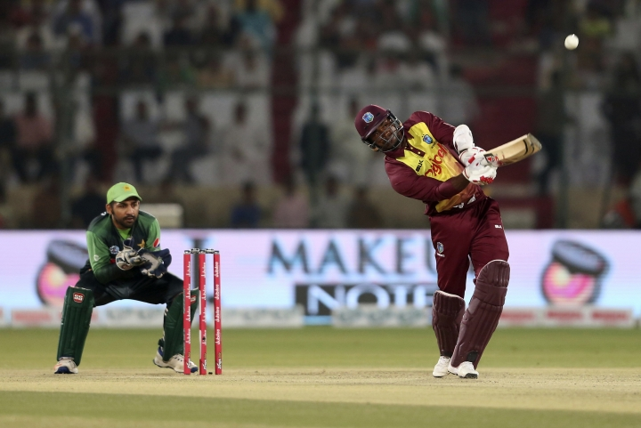 West Indies captain Jason Mohammad hits boundary as Pakistani wicketkeeper and captain Sarfraz Ahmed looks on during the final of the Twenty20 match in Karachi, Pakistan, Tuesday, April 3, 2018. (AP Photo/Shakil Adil)
