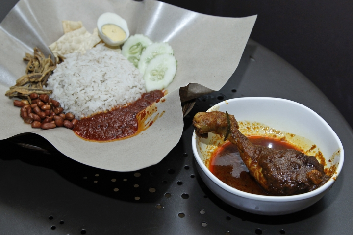 Malaysia's national dish, Nasi Lemak and chicken rendang, at a restaurant in Subang Jaya, Malaysia, Tuesday, April 3, 2018. Judges on a popular British cooking show are being ridiculed for ignorance of Asian food after insisting a Malaysian contestant's chicken rendang curry should have been crispy, and have taken to social media to denounce the TV show hosts. (AP Photo/Sadiq Asyraf)