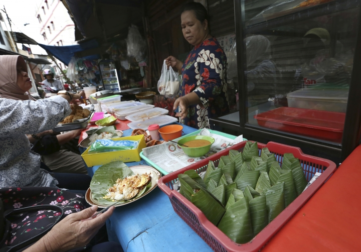 Customers eat nasi uduk, which is Indonesian style steamed rice cooked in coconut milk dish, at a street food stall in Jakarta, Indonesia. Tuesday, April 3, 2018. Judges on a popular British cooking show are being ridiculed for ignorance of Asian food after insisting the chicken in a Malaysian contestant's rendang curry should have been crispy. (AP Photo/Tatan Syuflana)