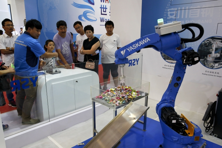 "In this Aug. 23, 2017, photo, an exhibitor demonstrates a Chinese-made industrial robot to visitors at the World Robot Conference at the Yichuang International Conference and Exhibition Centre in Beijing. China On Wednesday, April 4, 2018 vowed to take measures of the ""same strength"" in response to a proposed U.S. tariff hike on $50 billion worth of Chinese goods in a spiraling dispute over technology policy that has fueled fears it might set back a global economic recovery. The Commerce Ministry said it would immediately challenge the U.S. move in the World Trade Organization. (AP Photo/Andy Wong)"