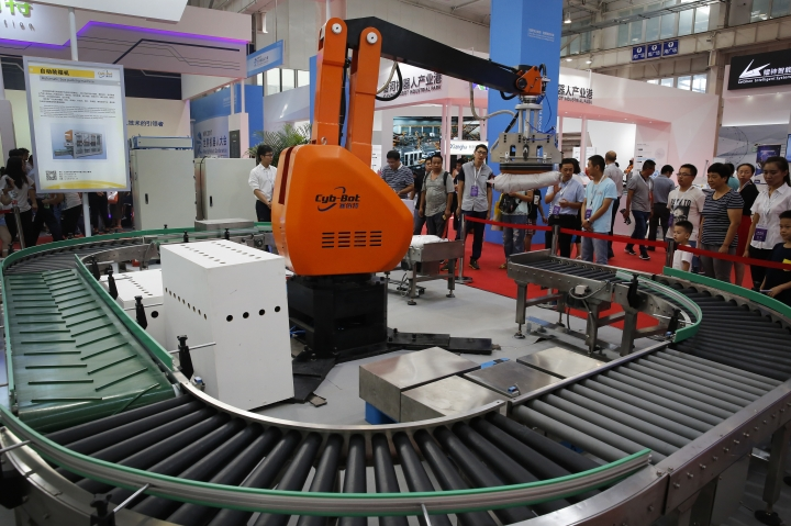 """In this Aug. 23, 2017, photo, visitors watch a Chinese-made industrial robot demonstrating on lifting goods during the World Robot Conference at the Yichuang International Conference and Exhibition Centre in Beijing. China On Wednesday, April 4, 2018 vowed to take measures of the """"same strength"""" in response to a proposed U.S. tariff hike on $50 billion worth of Chinese goods in a spiraling dispute over technology policy that has fueled fears it might set back a global economic recovery. The Commerce Ministry said it would immediately challenge the U.S. move in the World Trade Organization. (AP Photo/Andy Wong)"""