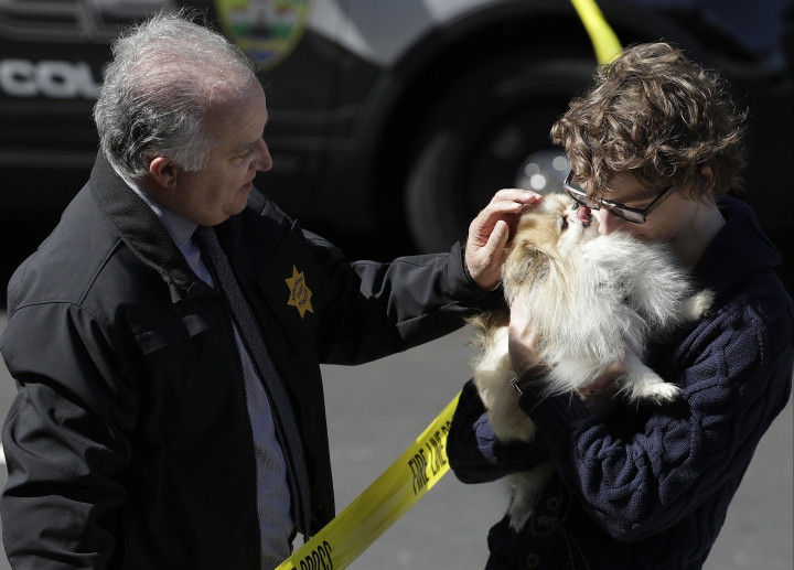 Burlingame Chief of Police Eric Wollman, left, hands a dog named Kimba to a man who wished to remain unidentified but said he worked for YouTube, outside the company's headquarters, in San Bruno, Calif., Tuesday, April 3, 2018. A woman opened fire at YouTube headquarters Tuesday, setting off a panic among employees and wounding several people before fatally shooting herself, police and witnesses said. (AP Photo/Jeff Chiu)