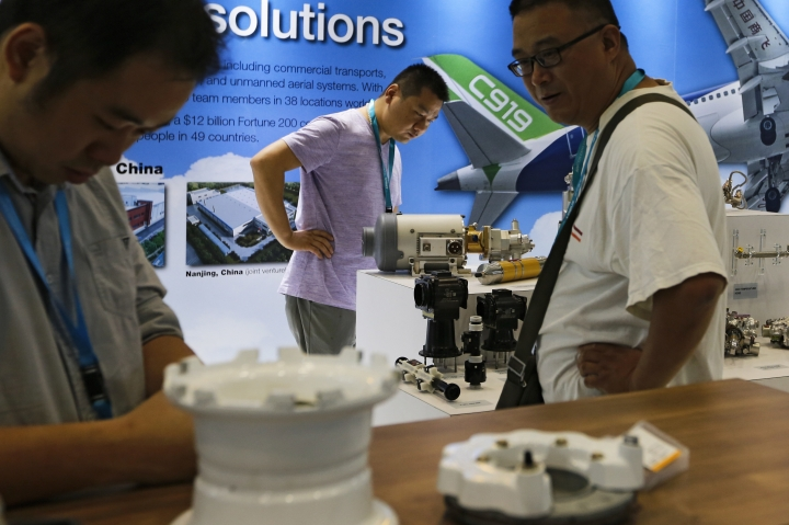 "In this Sept. 20, 2017, photo, visitors look at airplane component parts on display at Aviation Expo China in Beijing. China On Wednesday, April 4, 2018 vowed to take measures of the ""same strength"" in response to a proposed U.S. tariff hike on $50 billion worth of Chinese goods in a spiraling dispute over technology policy that has fueled fears it might set back a global economic recovery. The Commerce Ministry said it would immediately challenge the U.S. move in the World Trade Organization. (AP Photo/Andy Wong)"