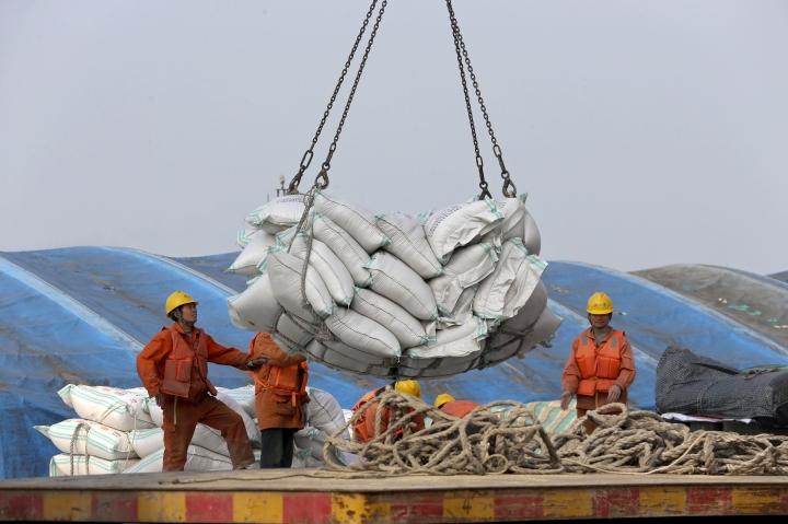 "In this March 22, 2018, photo, workers load imported soybeans at a port in Nantong in east China's Jiangsu province. China on Wednesday, April 4, 2018 vowed to take measures of the ""same strength"" in response to a proposed U.S. tariff hike on $50 billion worth of Chinese goods in a spiraling dispute over technology policy that has fueled fears it might set back a global economic recovery. The Commerce Ministry said it would immediately challenge the U.S. move in the World Trade Organization. (Chinatopix via AP)"