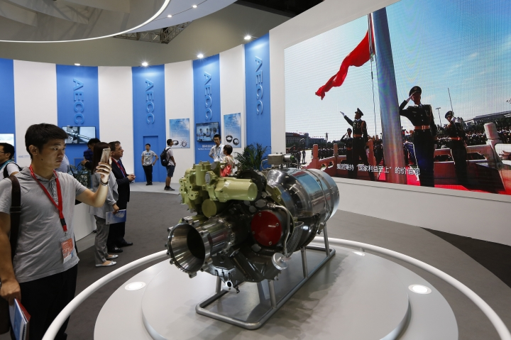 "In this Sept. 20, 2017, photo, visitors look at aircraft component parts on display near a screen showing the China's flag raising ceremony, at Aviation Expo China in Beijing. China On Wednesday, April 4, 2018 vowed to take measures of the ""same strength"" in response to a proposed U.S. tariff hike on $50 billion worth of Chinese goods in a spiraling dispute over technology policy that has fueled fears it might set back a global economic recovery. The Commerce Ministry said it would immediately challenge the U.S. move in the World Trade Organization. (AP Photo/Andy Wong)"