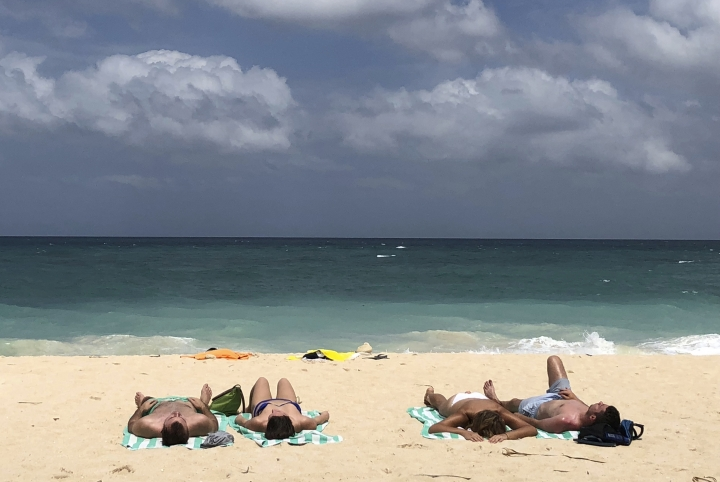 "In this March 12, 2018, photo, foreign tourists sunbathe at a beach on Boracay island, central Aklan province, Philippines. Philippine officials say the president has approved the closure of Boracay island, the country's most famous beach resort, for up to six months after he said it has turned into a ""cesspool."" (AP Photo/Aaron Favila)"