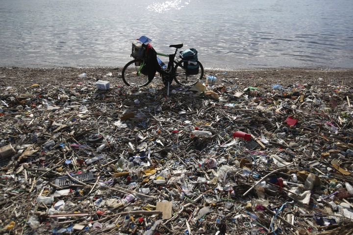 In this Wednesday, Jan. 17, 2018 photo a bicycle is parked next to plastics and other garbage on a beach in Neo Faliro, southern Athens. Greece has the European Union's longest coastline, poor waste management and an addiction to single-use plastic that littering the country's seabed. To fight the problems, volunteer divers are working as underwater garbage collectors to clear debris - mostly plastic - that is littering the sea floor. (AP Photo/Thanassis Stavrakis)