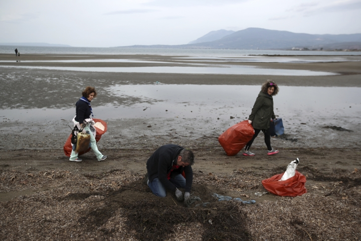 In this Saturday, Feb. 3, 2018, Spanish volunteer Fran Vargas digs the sand to pull out buried bag as others hold bags with garbage during a trash collection at Kolovrechtis wetland near Halkida, Evia island. Greece has the European Union's longest coastline, poor waste management and an addiction to single-use plastic that littering the country's seabed. To fight the problems, volunteer divers are working as underwater garbage collectors to clear debris - mostly plastic - that is littering the sea floor. (AP Photo/Thanassis Stavrakis)