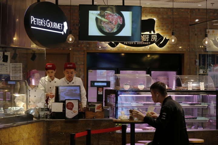 A man eats at a restaurant serving imported American beefs at a shopping mall in Beijing, Thursday, April 5, 2018. The United States and China, the world's two largest economies, have roiled financial markets and fueled fears of a protracted trade war by threatening tariffs this week on each other's goods. The United States on Tuesday said it would impose 25 percent duties on $50 billion of imports from China, and China quickly retaliated by listing $50 billion of products that it could hit with its own 25 percent tariffs. (AP Photo/Andy Wong)