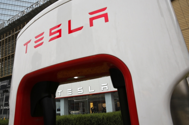 A sales person stands inside a Tesla electric vehicle showroom in Beijing, Thursday, April 5, 2018. The United States and China, the world's two largest economies, have roiled financial markets and fueled fears of a protracted trade war by threatening tariffs this week on each other's goods. The United States on Tuesday said it would impose 25 percent duties on $50 billion of imports from China, and China quickly retaliated by listing $50 billion of products that it could hit with its own 25 percent tariffs. (AP Photo/Andy Wong)