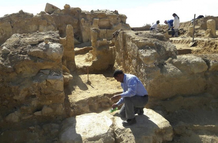 This undated photo released by the Egyptian Ministry of Antiquities shows archeologists working at the site of the remains of a temple dating back to the Greco-Roman period in the country's western desert, some 31 miles, 50 km, west of Siwa Oasis, Egypt. The ministry said the uncovered part include stone walls and the temple's main entrance which leads to courtyard and entrances to other chambers. (Egyptian Ministry of Antiquities via AP)