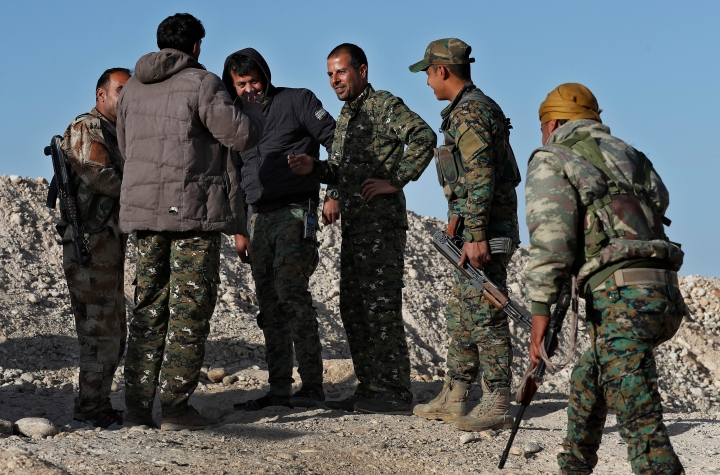 """FILE - In this Thursday, March 29, 2018 file photo, commander Abu Ali Nejm, third right, of the U.S-backed Syrian Manbij Military Council, speaks with his fighters at the front line against Turkish-backed fighters, north of Manbij, Syria. Even as President Donald Trump mulls a U.S. pullout, insisting that the Islamic State is """"almost completely defeated,"""" the extremist group is showing signs of resurgence in Syria. Talk of a U.S. troop withdrawal has alarmed the Unites States' main ally in Syria, the Kurds, who fought alongside the Americans to roll back the Islamic State group. (AP Photo/Hussein Malla, File)"""