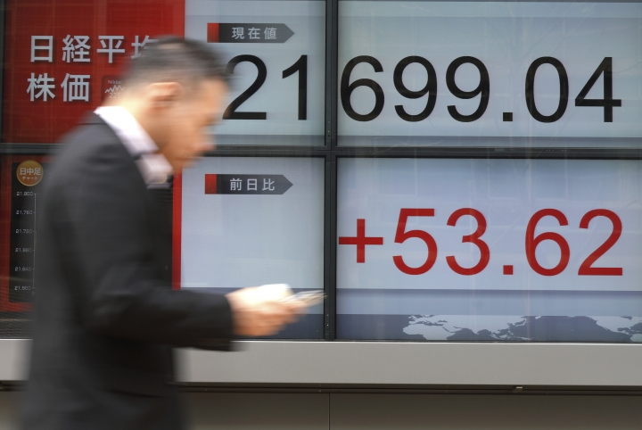 A man walks past an electronic stock board showing Japan's Nikkei 225 index at a securities firm in Tokyo Friday, April 6, 2018. Most Asian stock markets slipped Friday after the Trump administration threatened yet more tariffs on Chinese imports, adding to investor fears of a brewing trade battle between the world's two biggest economies. (AP Photo/Eugene Hoshiko)
