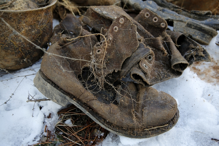 In this Dec. 3, 2015, photo, a pair of boots and a helmet, which village elders claim belong to soldiers who fought in the Korean War, is laid out next to a burial site on Ryongyon-ri hill in Kujang county, North Korea. Nearly 7,800 U.S. troops remain unaccounted for from the Korean War. About 5,300 were lost in North Korea. More than six decades after they died for their country, the repatriation of the remains of thousands of U.S. troops missing in action and presumed dead from the Korean War may finally get a boost now that U.S. President Donald Trump and North Korean leader Kim Jong Un are expected to hold the first-ever summit between their two countries. (AP Photo/Wong Maye-E)