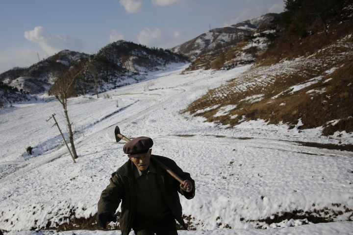 In this Dec. 3, 2015, photo, village elder Song Hong Ik, carries his shovel as he walks past Ryongyon-ri hill on his right, where remains of soldiers he claims fought in the Korean War are buried in Kujang county, North Korea. Nearly 7,800 U.S. troops remain unaccounted for from the Korean War. About 5,300 were lost in North Korea. More than six decades after they died for their country, the repatriation of the remains of thousands of U.S. troops missing in action and presumed dead from the Korean War may finally get a boost now that U.S. President Donald Trump and North Korean leader Kim Jong Un are expected to hold the first-ever summit between their two countries. (AP Photo/Wong Maye-E)