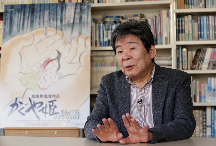 """In this Feb. 12, 2015 photo, Japanese animated film director Isao Takahata speaks about his latest film """"The Tale of The Princess Kaguya"""" with its poster during an interview at his office, Studio Ghibli, in suburban Tokyo. Takahata, co-founder of the prestigious Japanese animator Studio Ghibli that stuck to a hand-drawn """"manga"""" look in the face of digital filmmaking, has died. He was 82. Takahata, who directed """"Grave of the Fireflies,"""" a tragic tale about wartime childhood, died Thursday, April 5, 2018, of lung cancer at a Tokyo hospital, according to a studio statement. (AP Photo/Shizuo Kambayashi)"""