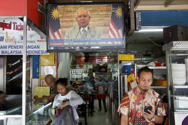 Passerby walks in front of a live broadcast of an announcement by Malaysian Prime Minister Najib Razak at a restaurant in Kuala Lumpur, Malaysia, Friday, April 6, 2018. Malaysia's Prime Minister Najib Razak says he'll dissolve Parliament on Saturday, April 7, 2018, paving the way for general elections expected to be held next month. (AP Photo/Sadiq Asyraf)