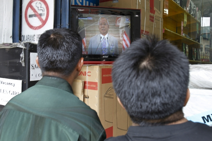 People watch a live broadcast of an announcement by Malaysian Prime Minister Najib Razak at an electrical shop in Kuala Lumpur, Malaysia, Friday, April 6, 2018. Malaysia's Prime Minister Najib Razak says he'll dissolve Parliament on Saturday, April 7, 2018, paving the way for general elections expected to be held next month. (AP Photo/Sadiq Asyraf)