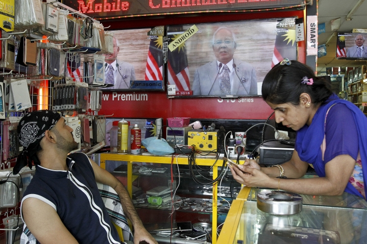 A shop vendor watches a live broadcast of an announcement by Malaysian Prime Minister Najib Razak at an electrical shop in Kuala Lumpur, Malaysia, Friday, April 6, 2018. Malaysia's Prime Minister Najib Razak says he'll dissolve Parliament on Saturday, April 7, 2018, paving the way for general elections expected to be held next month. (AP Photo/Sadiq Asyraf)