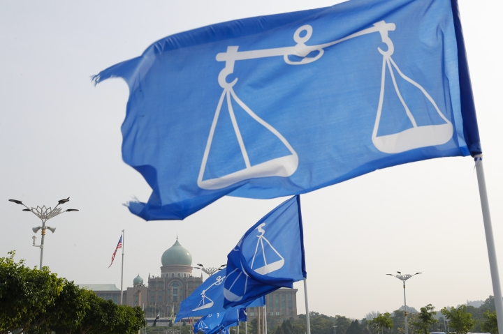 The flags of Malaysia's ruling party National Front coalition flutter in front of the Prime Minister office in Putrajaya, Malaysia, Friday, April 6, 2018. Prime Minister Najib Razak said in a nationally televised address that he obtained consent from Malaysia's king to dissolve Parliament on Saturday, April 7, 2018. (AP Photo/Vincent Thian)