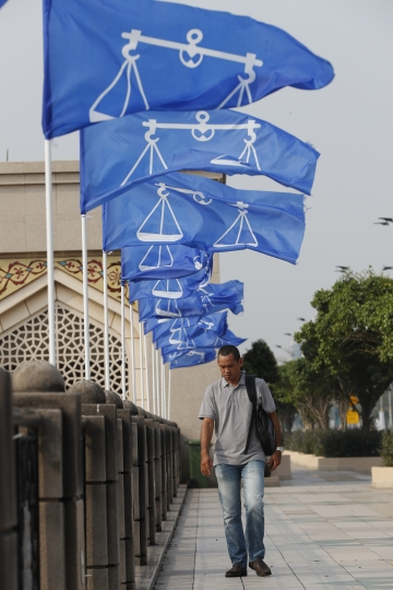 A man walks under the flags of Malaysia's ruling party National Front coalition near the Prime Minister's office in Putrajaya, Malaysia, Friday, April 6, 2018. Prime Minister Najib Razak said in a nationally televised address that he obtained consent from Malaysia's king to dissolve Parliament on Saturday, April 7, 2018.(AP Photo/Vincent Thian)