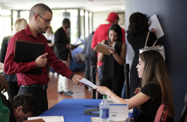 FILE- In this Jan. 30, 2018, file photo, an employee of Aldi, right, takes an application from a job applicant at a JobNewsUSA job fair in Miami Lakes, Fla. On Friday, April 6, the U.S. government issues the March jobs report. (AP Photo/Lynne Sladky, File)
