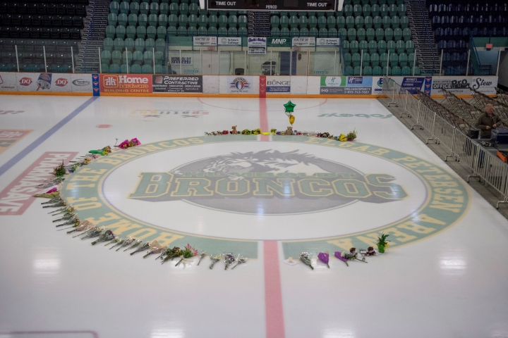 Flowers are shown at center ice as preparations are made at Elgar Petersen Arena for a vigil tonight in Humboldt, Saskatchewan, Sunday, April 8, 2018. Multiple people traveling with the Humboldt Broncos SJHL hockey team are dead, and many injured when their bus was collided with a semi-trailer north of Tisdale, Saskatchewan. (Liam Richards/The Canadian Press via AP)