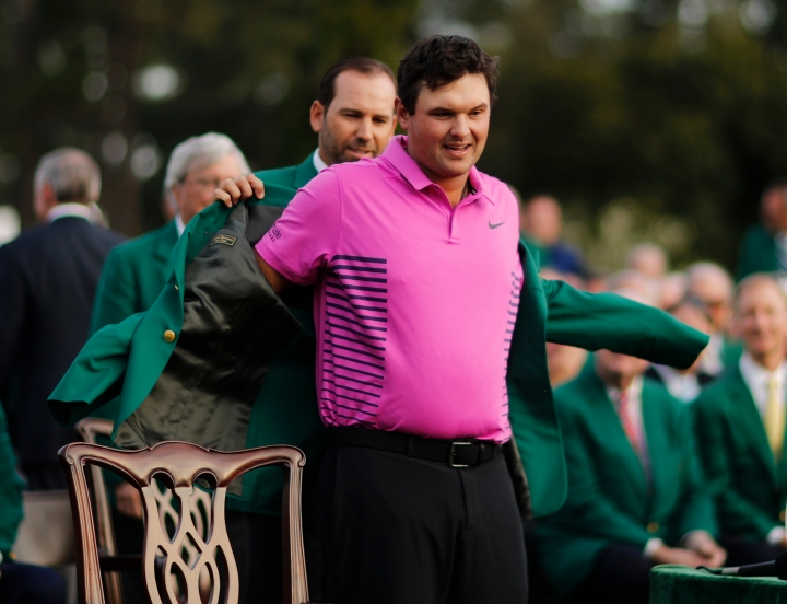 Former Masters champion Sergio Garcia, left , of Spain, helps Patrick Reed with his green jacket after winning the Masters golf tournament Sunday, April 8, 2018, in Augusta, Ga. (AP Photo/David Goldman)