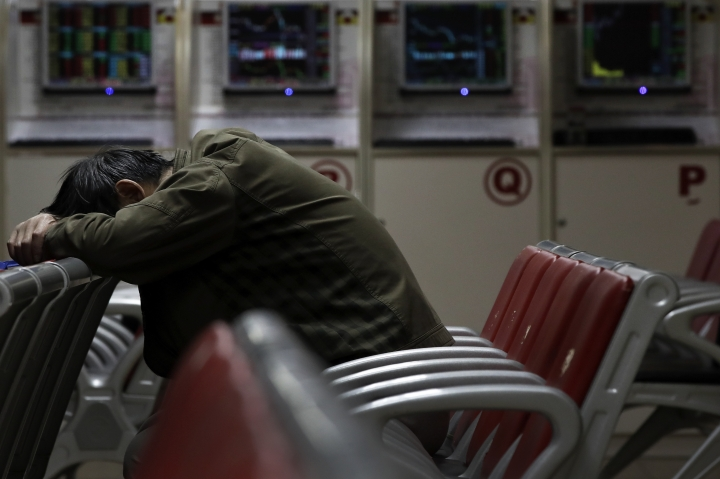 A man takes a nap at a brokerage house in Beijing, Monday, April 9, 2018. Asian stock markets rose Monday amid uncertainty about an escalating U.S.-Chinese tariff dispute after President Donald Trump said a settlement was possible but his advisers said other nations might add to pressure on Beijing. (AP Photo/Andy Wong)