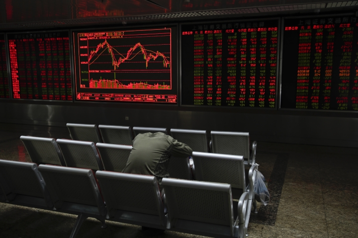 A man takes a nap near at an electronic board displaying stock prices at a brokerage house in Beijing, Monday, April 9, 2018. Asian stock markets rose Monday amid uncertainty about an escalating U.S.-Chinese tariff dispute after President Donald Trump said a settlement was possible but his advisers said other nations might add to pressure on Beijing. (AP Photo/Andy Wong)