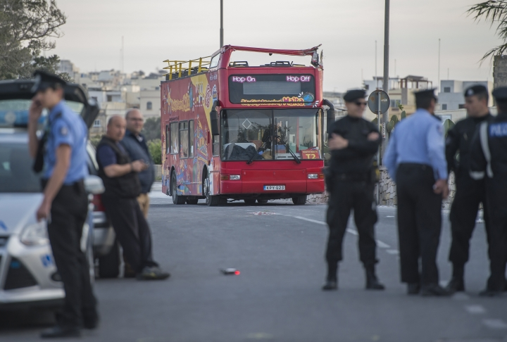 Police officers stand next to an open-top double-decker tourist bus that slammed into a low-hanging tree branch killing two people and injuring 45 others, including a dozen children, in the tourists destination of Zurrieq, near Valletta, Malta, Monday, April 9, 2018. Health Minister Chris Fearne said most of the passengers hailed from Belgium or Britain, though police said the seriously injured also included a German and Italian. (AP Photo/Rene Rossignaud)