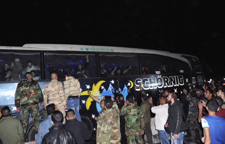 In this photo released by the Syrian official news agency SANA, soldiers and residents salute civilians after being released by the Army of Islam group that had been holding them since 2013, in Damascus, Syria, early Monday, April 9, 2018. Syrian state media is reporting that dozens of civilians who had been held for years by a rebel group near the capital Damascus have been freed. (SANA via AP)