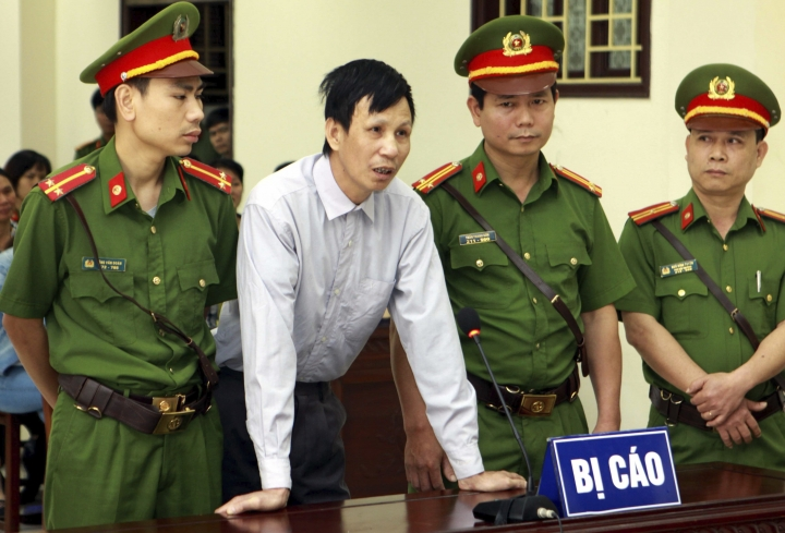 Activist Nguyen Van Tuc, center, stands trial in Thai Binh, Vietnam, Tuesday, April 10, 2018. Tuc was sentenced to 13 years in prison after being convicted of attempting to overthrow the government. (The Duyen/ Vietnam News Agency via AP)