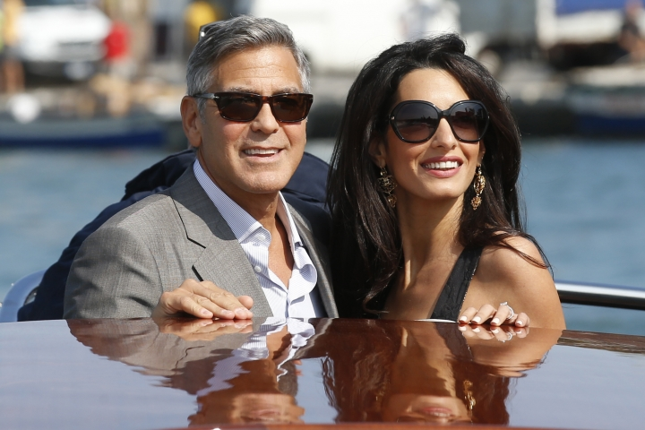 FILE - In this Sept. 26, 2014 file photo, George Clooney, left, and Amal Alamuddin arrive in Venice, Italy. Clooney and Alamuddin married in Venice, Italy in 2014. Their nuptials involved gondolas and mega-paparazzi. This after a courtship that made Alamuddin, now a Clooney, a high-profile fashion icon as she continues to pursue her career. (AP Photo/Luca Bruno, File)