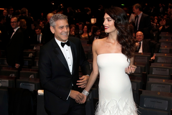 FILE - In this Feb. 24, 2017 file photo, actor George Clooney and his wife Amal Clooney arrive at the 42nd Cesar Film Awards ceremony in Paris. Clooney and Alamuddin married in Venice, Italy in 2014. Their nuptials involved gondolas and mega-paparazzi. This after a courtship that made Alamuddin, now a Clooney, a high-profile fashion icon as she continues to pursue her career. (AP Photo/Thibault Camus, File)