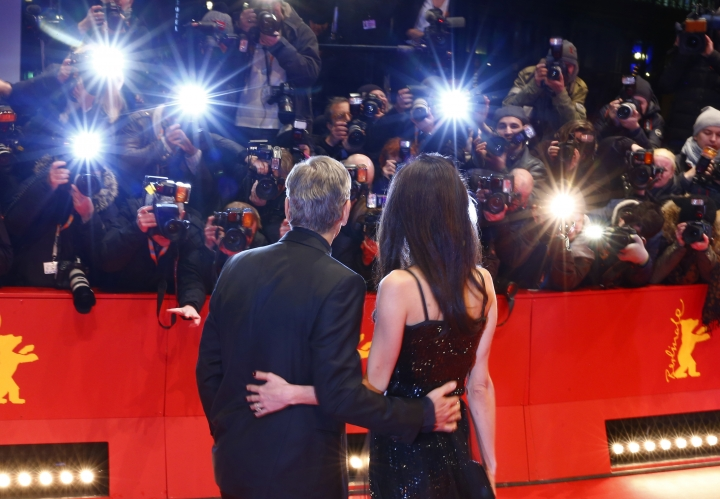 """FILe - In this Feb. 11, 2016 file photo, George Clooney, left, and his wife Amal Clooney arrive at the red carpet for """"Hail, Caesar!"""" at the 2016 Berlinale Film Festival in Berlin, Germany. Clooney and Alamuddin married in Venice, Italy in 2014. Their nuptials involved gondolas and mega-paparazzi. This after a courtship that made Alamuddin, now a Clooney, a high-profile fashion icon as she continues to pursue her career. (AP Photo/Axel Schmidt, File)"""