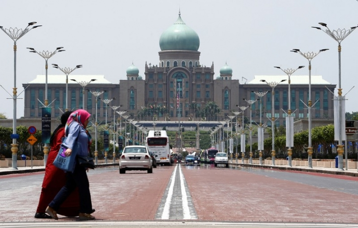 Women cross a road in front of the Prime Minister's office in Putrajaya, Malaysia April 5, 2018. Picture taken April 5, 2018. REUTERS/Lai Seng Sin