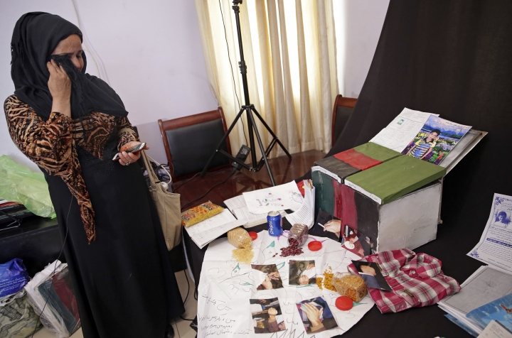 """In this March 31, 2018 photo, Adila Hamidi chokes back tears as she speaks about her son, 17-year-old Faisal who was killed in a suicide attack, while standing in front of mementos for his """"memory box,"""" part of an initiative designed by the Afghanistan Human Rights and Democracy Organization, in Kabul, Afghanistan. Survivors of Afghanistan's many wars have tucked memories of those they have lost inside boxes draped in a flag of their own creation that represents the Afghanistan of their dreams. These boxes are a tribute to those lost to war but also a healing balm for those left behind. (AP Photo/Massoud Hossaini)"""