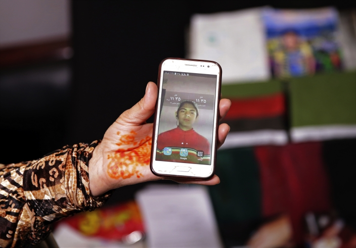 """In this March 31, 2018 photo, Adila Hamidi shows a photo of her son, 17-year-old Faisal who was killed in a suicide attack, while standing in front of mementos for his """"memory box,"""" part of an initiative designed by the Afghanistan Human Rights and Democracy Organization, in Kabul, Afghanistan. Survivors of Afghanistan's many wars have tucked memories of those they have lost inside boxes draped in a flag of their own creation that represents the Afghanistan of their dreams. The boxes are a tribute to those lost to war but also a healing balm for those left behind. (AP Photo/Massoud Hossaini)"""