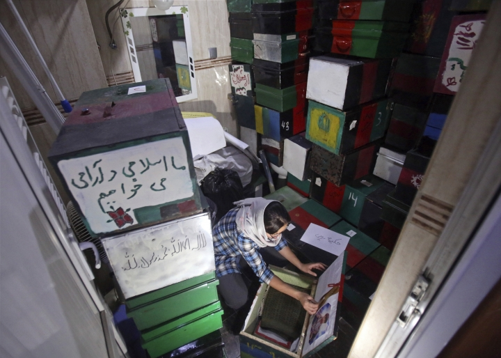 """In this Saturday, April 7, 2018 photo, Zahra Hossaini, a member of the Afghanistan Human Rights and Democracy Organization, arranges """"memory boxes,"""" among some 300 boxes stored in Kabul, Afghanistan. Survivors of Afghanistan's many wars have tucked memories of those they have lost inside boxes draped in a flag of their own creation that represents the Afghanistan of their dreams. The boxes are a tribute to those lost to war but also a healing balm for those left behind. (AP Photo/Rahmat Gul)"""