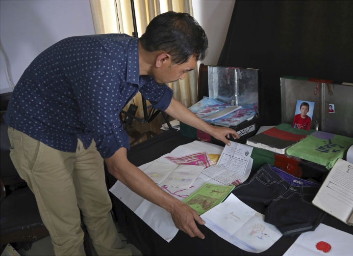In this Monday, April 2, 2018 photo, Salim Rajabi, project organizer, arranges mementos of Sayed Baqir, one of Afghanistan's war dead, who was killed in a suicide attack, to be photographed as part of a project known as the Memory Box Initiative, in Kabul, Afghanistan. Survivors of Afghanistan's many wars have tucked memories of those they have lost inside boxes draped in a flag of their own creation that represents the Afghanistan of their dreams. The boxes are a tribute to those lost to war but also a healing balm for those left behind. (AP Photo/Rahmat Gul)