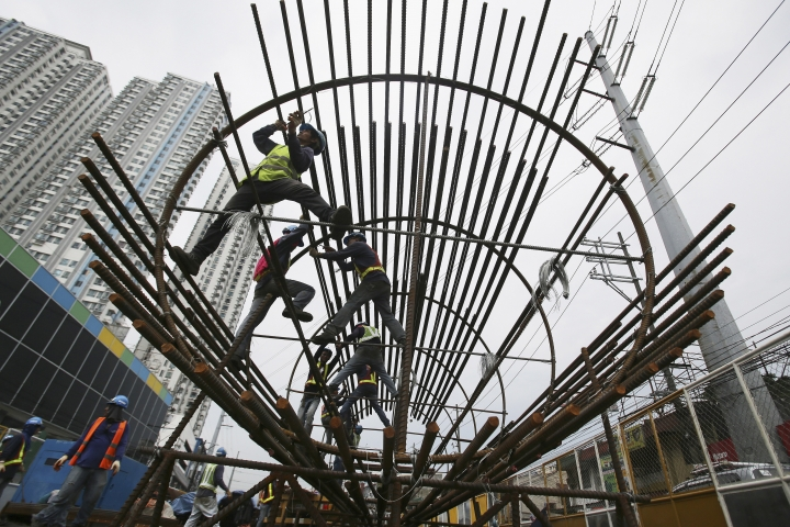 FILE - In this Aug. 12, 2015, file photo, workers arrange metal rods at a government road project in suburban Quezon City, north of Manila, Philippines. The Asian Development Bank said in a report Wednesday, April 11, 2018, the bank is forecasting that developing Asian economies will expand slightly faster than expected this year but warns U.S. trade tensions are a major risk to its forecast. (AP Photo/Aaron Favila, File)