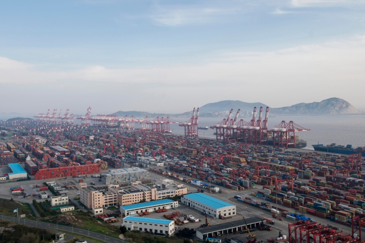 FILE - In this, March 29, 2018, file photo, a container ship is docked at the Yangshan port in Shanghai. The Asian Development Bank said in a report Wednesday, April 11, 2018, the bank is forecasting that developing Asian economies will expand slightly faster than expected this year but warns U.S. trade tensions are a major risk to its forecast. (AP Photo, File)