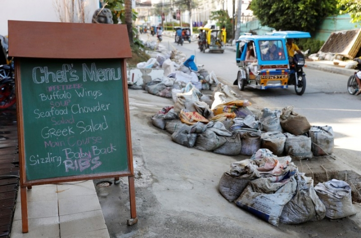 A menu on a board is pictured outside a restaurant near uncollected sacks containing waste from clogged sewage pipes along the main road on Boracay island, Philippines April 10, 2018. Picture taken April 10, 2018.  REUTERS/Erik De Castro